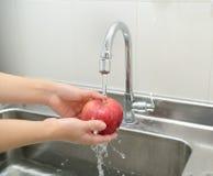 Frauenhände, die Apfel waschen Lizenzfreie Stockfotos