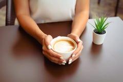 Frauenhände, die cappucino oder Lattekunst halten stockfotografie