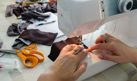 Frauenhände, die ein Kleidungsstück nähen lizenzfreie stockbilder