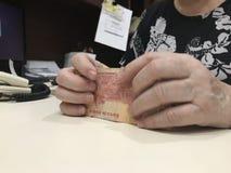 Frauenhände, die einen Stapel von 100 Banknoten des mexikanischen Pesos ergreifen lizenzfreies stockbild