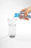Frauenhände, die frisches blaues Wasser gießen Lizenzfreie Stockbilder