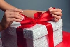 Frauenhände, die Geschenk halten Stockbild