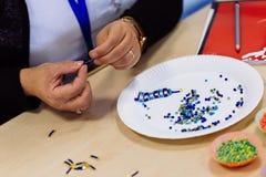 Frauenhände, die Perlenarmband herstellen Lizenzfreies Stockfoto
