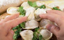 Frauenhände, die selbst gemachte ungekochte Ravioli halten Stockbilder