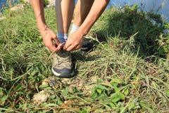 Frauenhände, die Spitze auf der Küste mountian binden lizenzfreie stockfotos