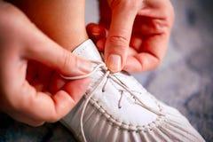 Frauenhände, die Spitzee auf weißem Schuh binden lizenzfreie stockfotografie