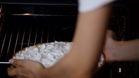 Frauenhände, die Törtchen für das Backen in den Ofen setzen stock video