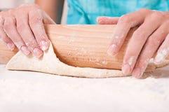 Frauenhände, die Teig auf der Tabelle mischen Stockbilder