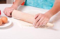 Frauenhände, die Teig auf der Tabelle mischen Lizenzfreie Stockfotos