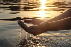 Frauenhände, die Wasser geben lizenzfreie stockbilder
