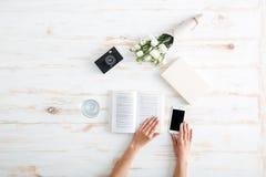 Frauenhände drehen Buchseiten auf dem hölzernen Schreibtisch um stockfotos