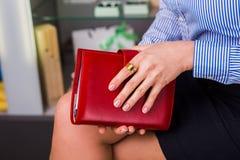 Frauenhände halten das rote Buch (Tagebuch), Nahaufnahme Lizenzfreie Stockfotografie