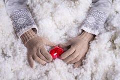 Frauenhände in helle Knickente gestrickten Handschuhen halten schönes entwirrtes rotes Herz der Weinlese in einem Schnee Lizenzfreies Stockbild