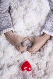 Frauenhände in helle Knickente gestrickten Handschuhen halten schönes entwirrtes rotes Herz der Weinlese in einem Schnee Stockbild