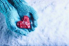 Frauenhände in helle Knickente gestrickten Handschuhen halten schönes entwirrtes rotes Herz der Weinlese in einem Schnee St.-Vale Lizenzfreie Stockbilder