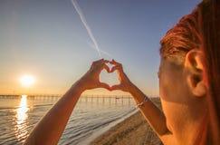 Frauenhände im Herzsymbol formten mit Sonnenunterganglicht stockbild