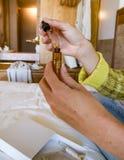Frauenhände mit einem Augentropfenzähler stockbilder
