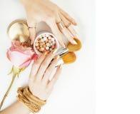 Frauenhände mit goldener Maniküre und vielen den Ringen, die Bürsten halten, lizenzfreie stockfotografie