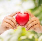 Frauenhände mit Herzen Stockfotos
