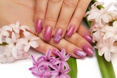 Frauenhände mit manikürten Nägeln und Blumen Stockbild