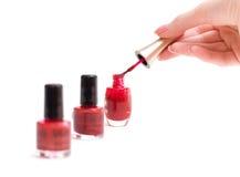 Frauenhände mit rotem Lack und Pinsel Lizenzfreies Stockfoto