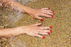 Frauenhände mit roten Nägeln in den Wellen Stockfoto