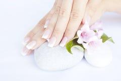 Frauenhände mit schönen Nägeln der französischen Maniküre Lizenzfreie Stockfotografie