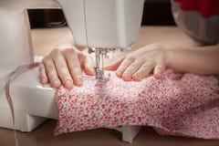 Frauenhände an Nähmaschine Stockfotos