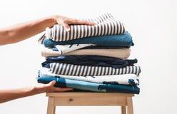 Frauenhände nehmen Stapel der blauen und beige Wäscherei lizenzfreie stockfotos