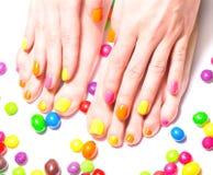 Frauenhände und -füße mit hellen Süßigkeiten herum Stockbild