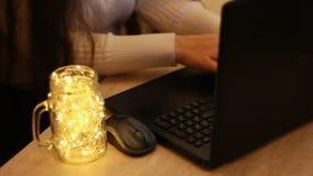 Frauenhände unter Verwendung des Computerlaptops auf dem Schreibtisch zu Hause Innen Hintergrund mit bokeh Leuchten stock footage