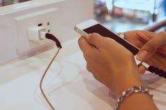Frauenhände unter Verwendung des Handys bei der Aufladung, Gefahr, Technolog lizenzfreie stockfotos