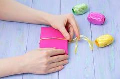 Frauenhände wickelten in einer rosa Geschenkbox mit einem hölzernen Hintergrund des gelben Bandveilchens ein Cose-up stockfoto