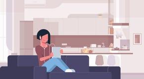 Frauenhörendes Audiobuch durch brunette Mädchen der Kopfhörer unter Verwendung der Tablette, die auf Couchmodernem Hauptkücheninn lizenzfreie abbildung