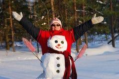 Frauenhaltungen mit Schneemann Lizenzfreies Stockfoto