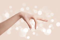 Frauenhand auf braunem Hintergrund Stockfotos