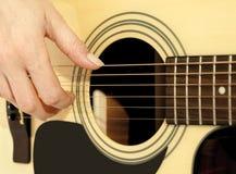 Frauenhand auf einer Akustikgitarre Stockbild