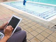 Frauenhand auf iPad nahe Swimmingpool Lizenzfreie Stockfotos