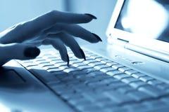 Frauenhand auf Laptoptastatur Stockfotos