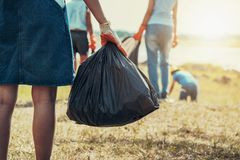 Frauenhand, die Abfall aufheben und Hand, die schwarze Tasche am Park hält lizenzfreie stockfotos