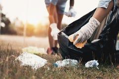 Frauenhand, die Abfallplastik für das Säubern aufhebt stockfotografie