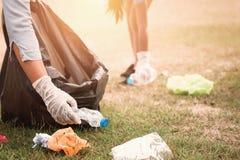 Frauenhand, die Abfallplastik für das Säubern aufhebt stockbilder