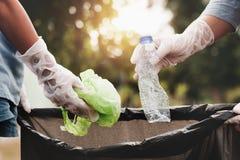 Frauenhand, die Abfallplastik für das Säubern aufhebt lizenzfreie stockfotografie