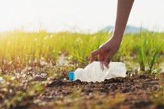 Frauenhand, die Abfallplastik für das Säubern in Fluss aufhebt stockfotos