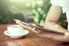 Frauenhand, die auf digitaler Tablette in der Kaffeestube hält und schaut Stockfotos