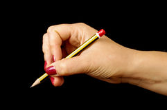 Frauenhand, die Bleistift auf dem schwarzen Hintergrund hält Stockbilder
