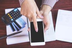 Frauenhand, die das intelligente Telefon berechnet ihre Monatsausgaben mit Kreditkarte, Sparkontobuch, Fristenkalenderkonzept FO  Stockbilder