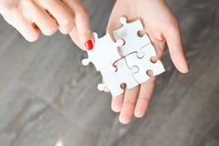 Frauenhand, die das rechte Stück des Puzzlespiels Geschäftsvernetzungskonzept vorschlagend passt Lizenzfreie Stockbilder