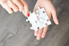 Frauenhand, die das rechte Stück des Puzzlespiels Geschäftsvernetzungskonzept vorschlagend passt Lizenzfreie Stockfotos