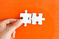 Frauenhand, die das rechte Stück des Puzzlespiels Geschäftsvernetzungskonzept vorschlagend passt Lizenzfreie Stockfotografie